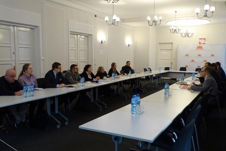 zdjęcie: kilka osób siedzi przy białym stole