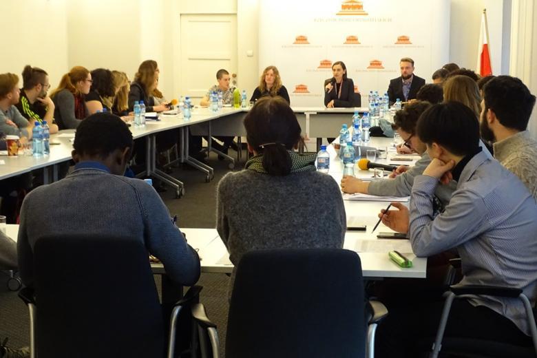 zdjęcie: kilkanaście osób siedzi przy złączonych stołach