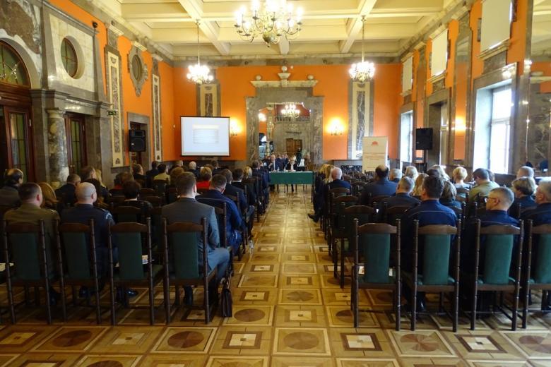 zdjęcie: na prost dwie osoby siedzą przy stole, po lewej i prawej stronie kilkadziesiąt osób siedzi na krzesłach
