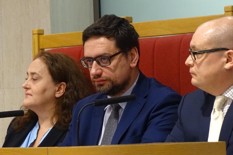 zdjęcie: za stołem siedzy dwóch mężczyzn i kobieta