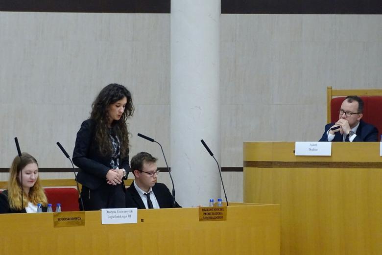 zdjęcie: po lewej stronie siedzą trzy osoby, obok za stołem trybunalskim siedzi mężczyzna