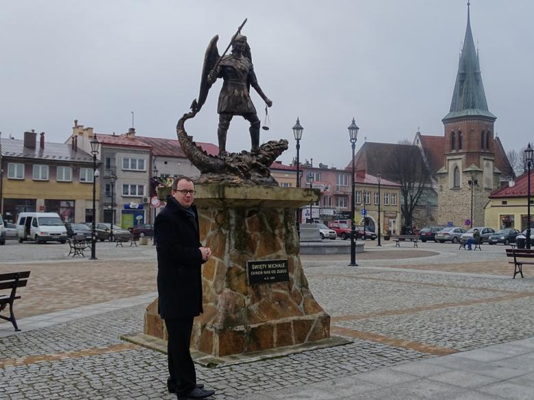 Mężczyzna przed pomnikiem św. Jerzego