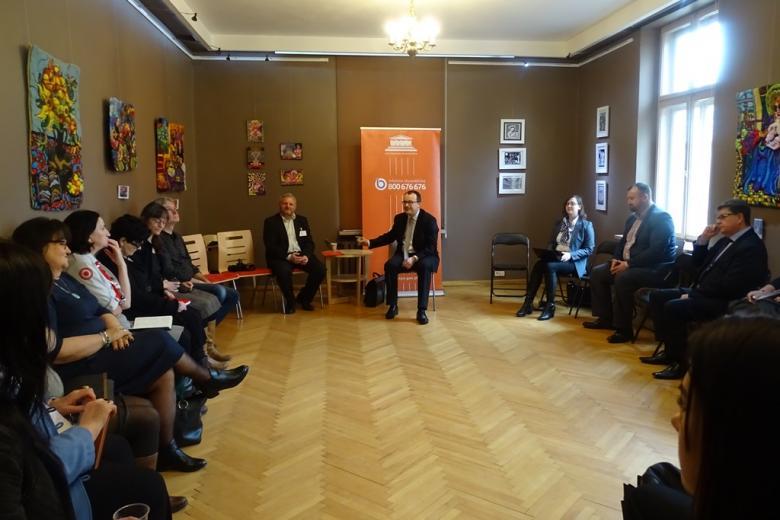 Zdjęcie: ludzie siedzą w kregu, Adam Bodnar na tle pomarańczowego loga RPO