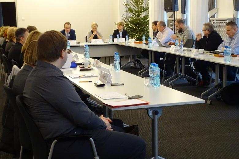 zdjęcie: za stołami ustawionymi w kształt litery U siedzi kilkanaście osób