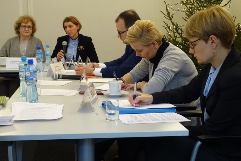 zdjęcie: przy stole bokiem siedzą dwe kobiety i mężczyzna, na wprost siedzią dwie kobiety