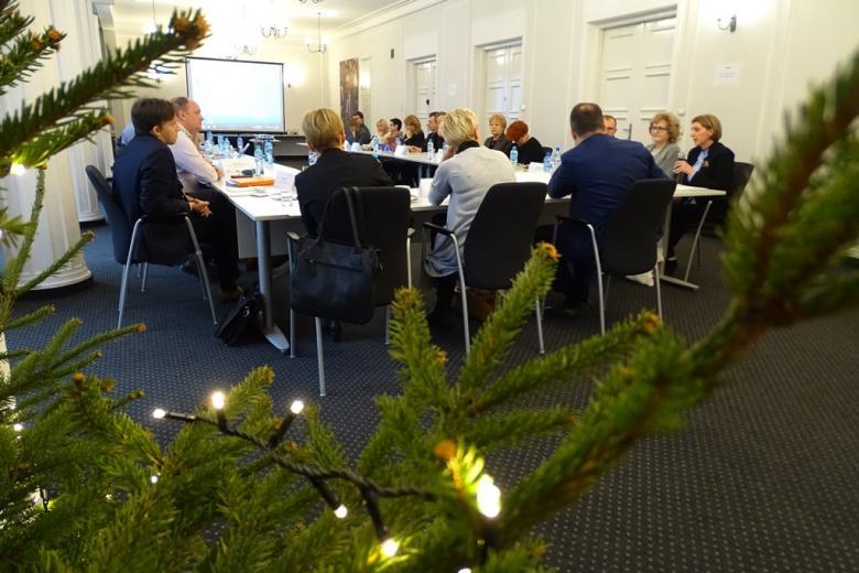 zdjęcie: na pierwszym planie widać fragmenty choinki i światełek, zzanich widać kilkanaście osób siedzących przy stołach