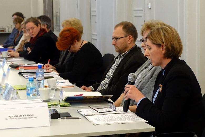 zdjęcie: kilka osób siedzi przy stole, kobieta na pierwszym planie mówi do mikrofonu