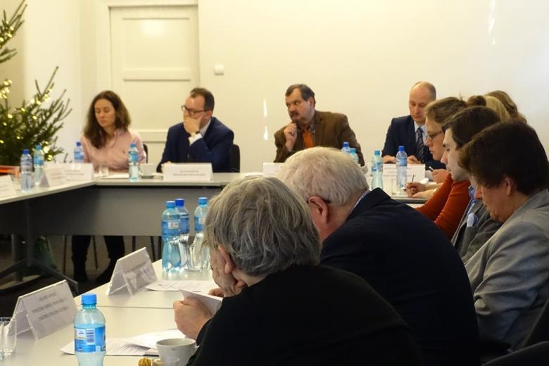 zdjęcie: kilka osób siedzi przy biały stołach, spoglądają w lewą stronę