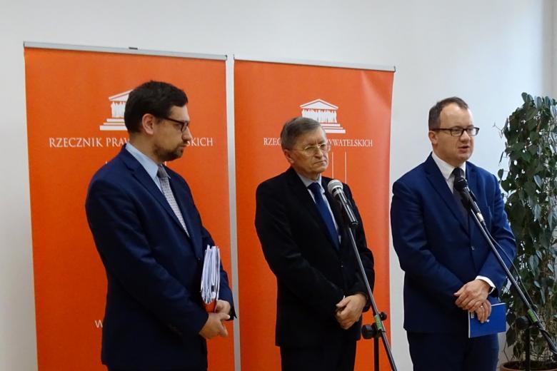 zdjęcie: trzech mężczyzn w garniturach stoi na tle pomarańczowych banerów