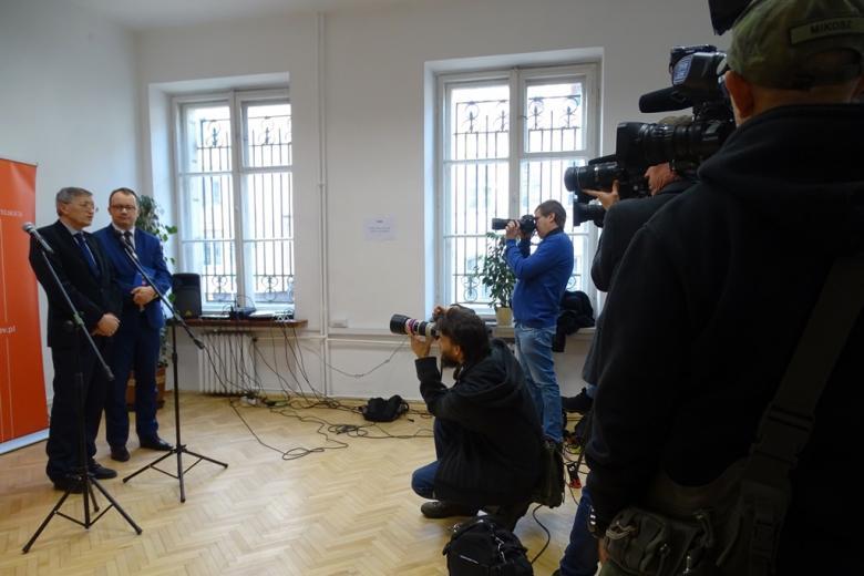 zdjęcie: po prawej stronie widać kilkunastu dziennikarzy z aparatami i kamerami, po lewej stronie stoi dwóch mężczyzn w garniturach