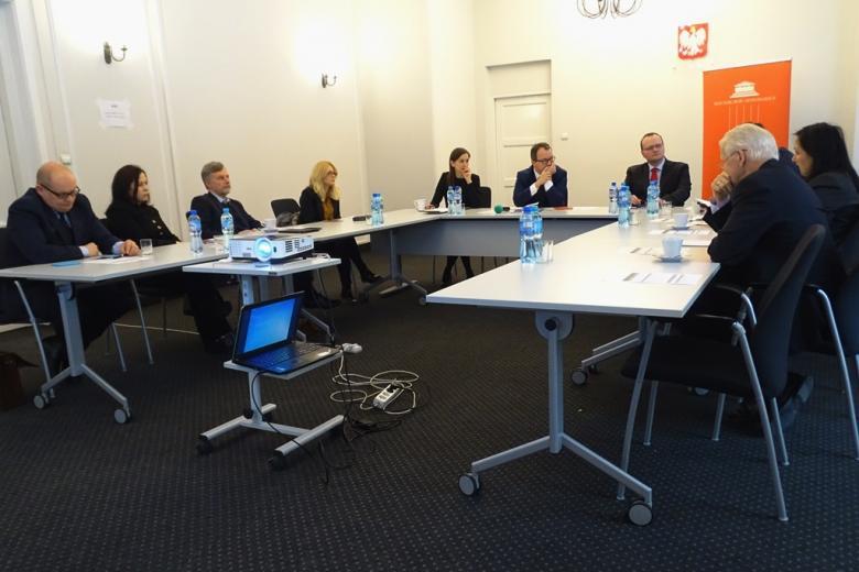 zdjęcie: kilka osób siedzi przy stołach ustawionych w kształcie litery U