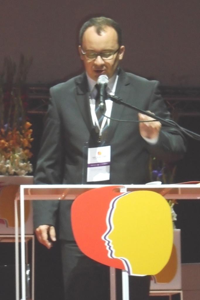 widać: rzecznika praw obywatelskich dr. Adama Bodnara, który trzyma statyw mikrofonu i przemawia do uczestników wydarzenia zza szklanej mównicy z logo Kongresu Kobiet