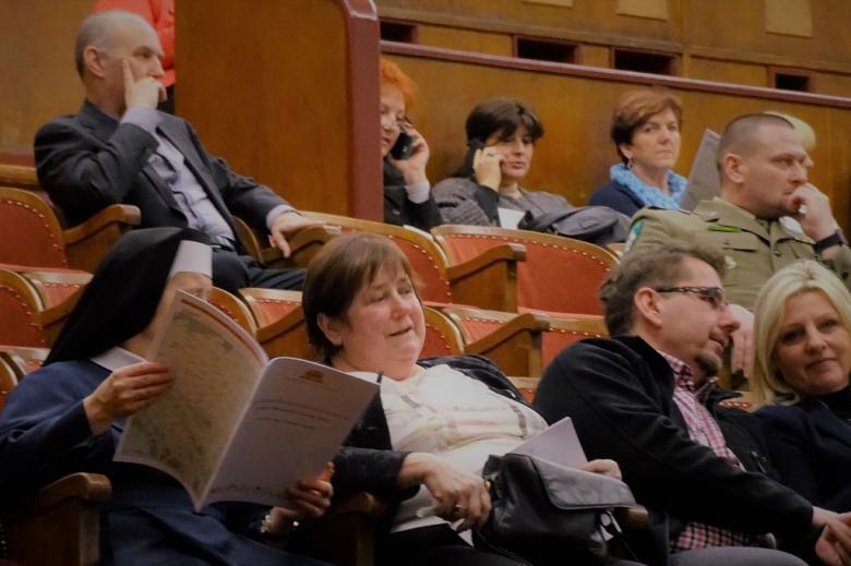 zdjęcie: na pierwszym planie zakonnica czyta broszurę obok niej siedzi kilka osób