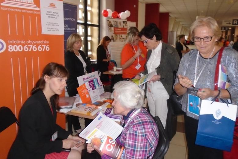 widać: siedzące przy stoliku dwie kobiety - starszą i młodszą, które ze sobą rozmawiają, za plecami pracowniczki biura stoi roll up z logo i numerem infolinii RPO (białe napisy na pomarańczowym tle) i inni uczestnicy wydarzenia