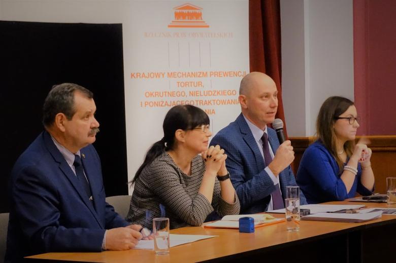 zdjęcie: za stołem siedzą dwie kobiety i dwaj mężczyźni, jeden z nich mówi do mikrofonu