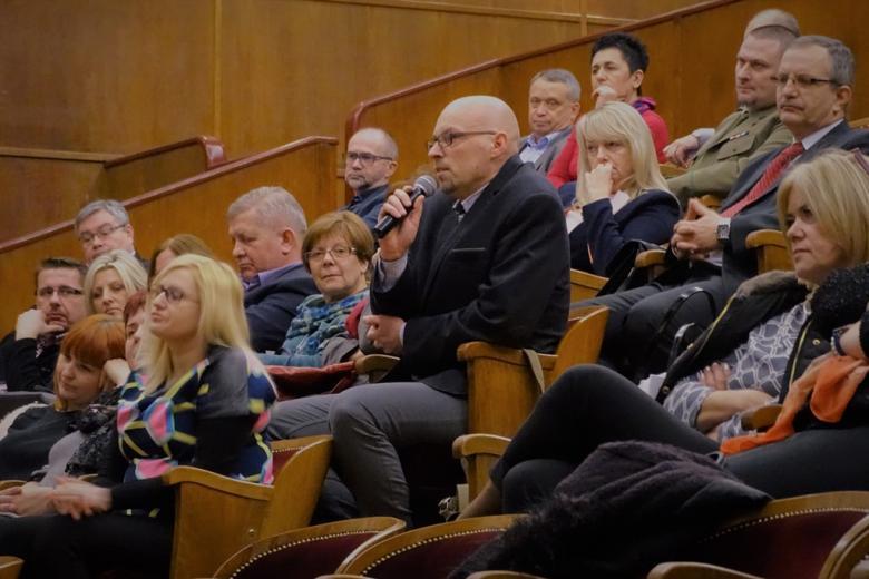 zdjęcie: klika osób siedzi na auli, jeden z mężczyzn mówi do mikrofonu