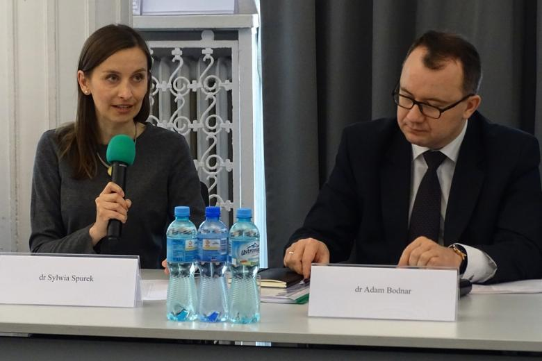 zdjęcie: przy stole po lewej stronie siedzi kobieta, która mówi do mikrofonu, obok niej siedzi mężczyzna, który notuje