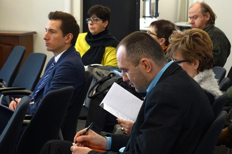 zdjęcie: kilka osób siedzi na krzesłach, niektórzy robią notatki