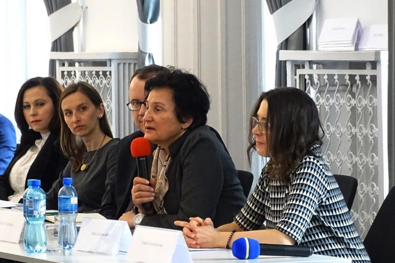 zdjęcie: przy stole siedzą cztery kobiety i jeden mężczyzna, jedna z kobiet mówi do mikrofonu