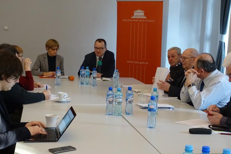 zdjęcie: kilka osób siedzi przy złączonych białych stołach, na wprost kobieta i mężczyzna