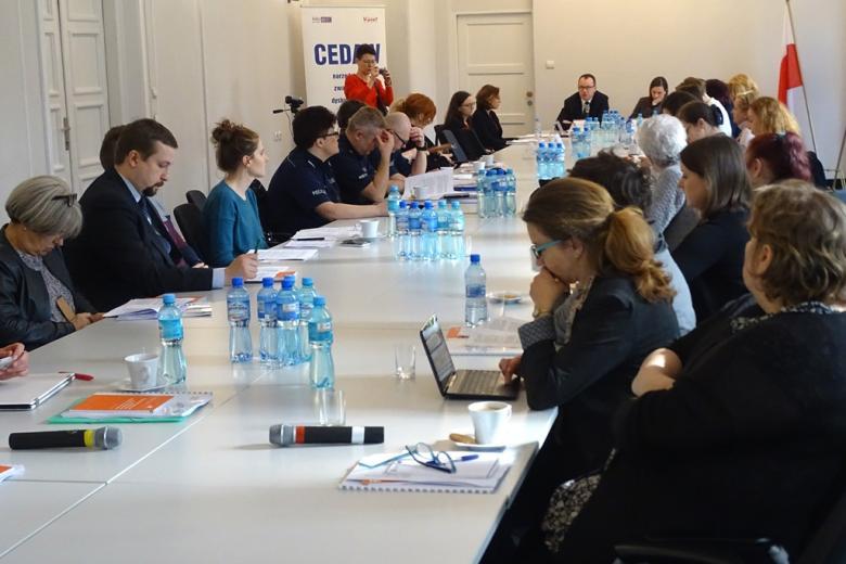 zdjęcie: około trzydzieści osób siedzi przy podłużnym stole, kobieta w czerwonym swetrze robi zdjęcie