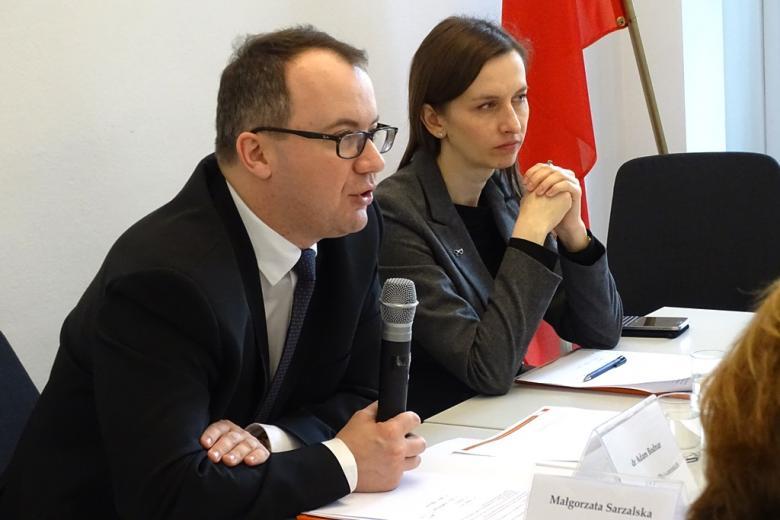 zdjęcie: mężczyzna i kobieta siedzą za stołem, mężczyzna mówi do mikrofonu