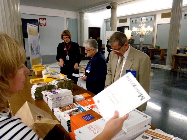 na zdjęciu uczestnicy Obywatelskiego Parlamentu Seniorów zapoznają się z publikacjami Biura RPO