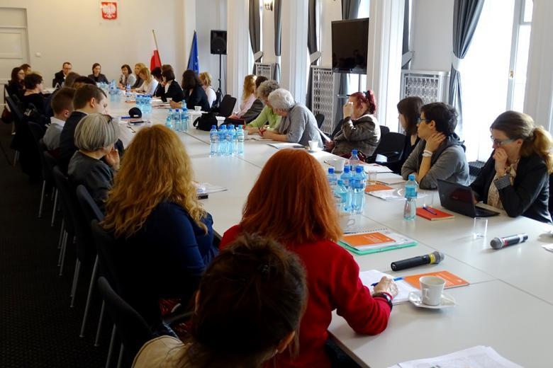 zdjęcie: około trzydzieści osób siedzi przy podłużnym stole