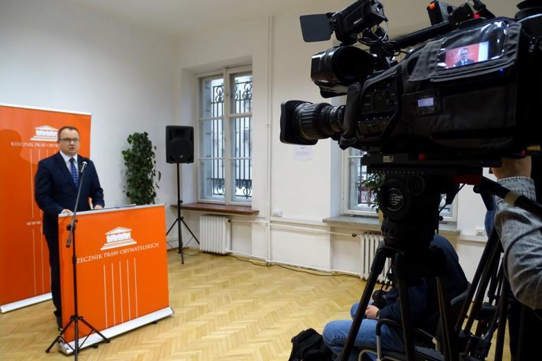 zdjęcie: po lewej stronie widać mężczyznę stojącego za pulpitem przy mikrofonie, po prawej stronie kawałek kamery telewizyjnej