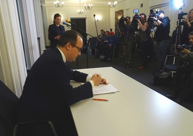 Mężczyzna składa podpis na dokumencie