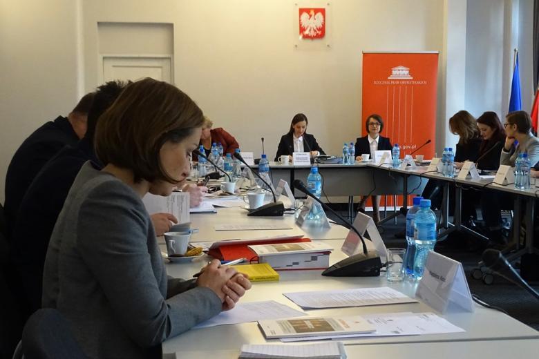 zdjęcie: przy białych stołach ustawionych naprzeciwsiebie siedzi kilkanaście osób, u szczytu trzy kobiety