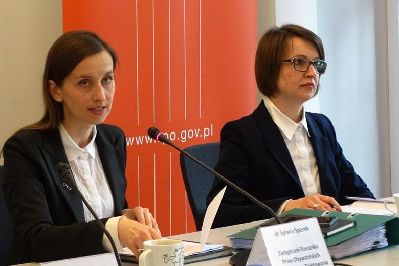 zdjęcie: dwie kobiety siedzą przy stole, koebieta po lewsj stronie mówi do mikrofonu, za nimi widać pomarańczowy baner