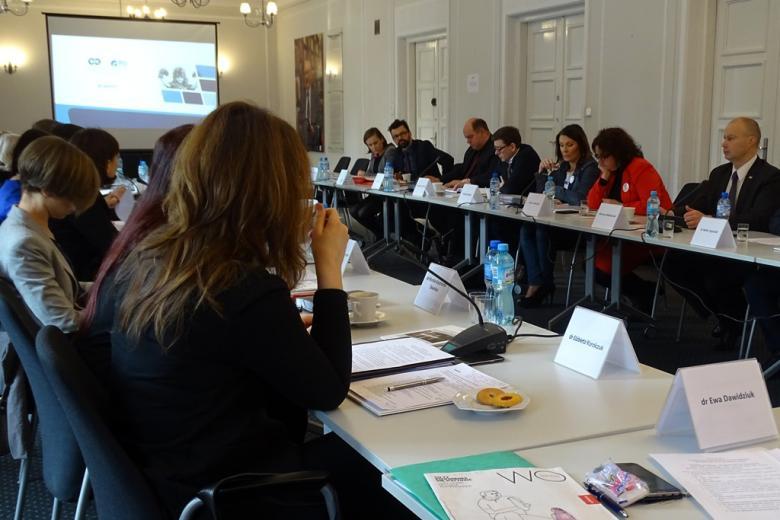 zdjęcie: przy białych stołach ustawionych naprzeciwsiebie siedzi kilkanaście osób, jeden z mężczyzn mówi do mikrofonu