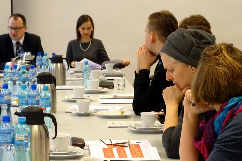 zdjęcie: w tle widać mężczyznę i kobietę siedzących u szczytu stołu, po prawej stronie siedzi kilka osób, kobieta czyta dokument
