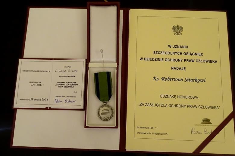 zdjęcie: teczka z dyplomem poświadczającym przyznanie odzanaki honorowej RPO oraz sama odznaka
