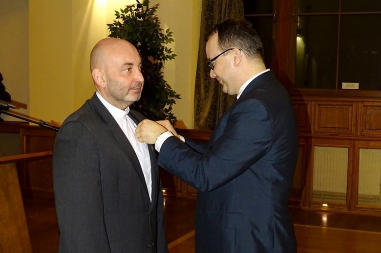 zdjęcie: dwóch mężczyzn w garniturach, mężczyzna po prawej stronie przypina odznakę drugiemu mężczyźnie