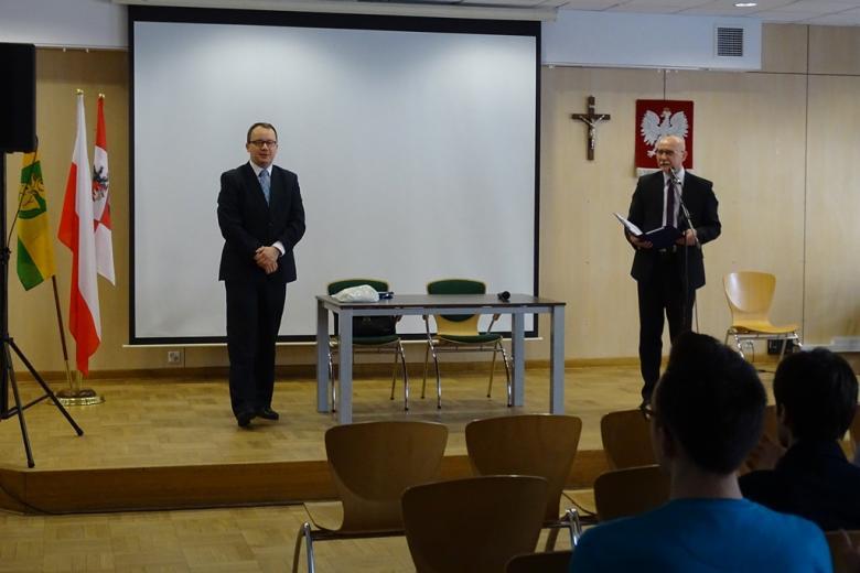 zdjęcie: na scenie stoi dwóch mężczyzn, za nimi jest tablica