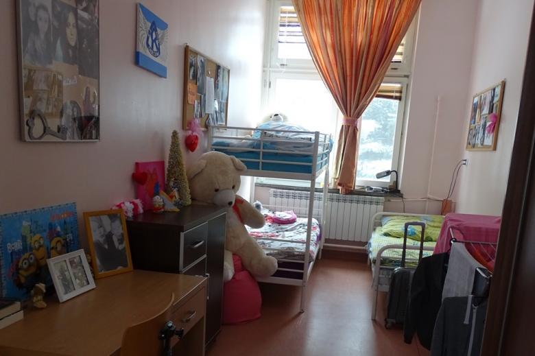 zdjęcie: wnetrze pokoju, w nim łóżko piętrowe stojące pod oknem, biurko, kolorowa firanka