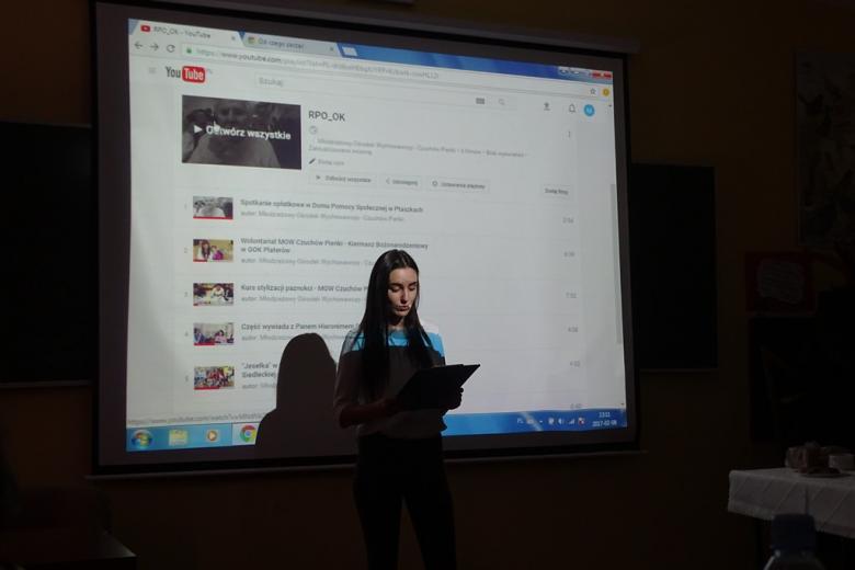 zdjęcie: na pierwszym planie stoi młoda dziweczyna, za nią jest rzutnik, na którym wyświetlane są filmy