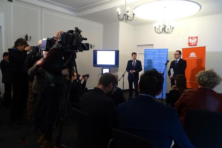 zdjęcie: na pierwszym planie stoją kamery, obok nich dziennikarze, przed nimi dwóch mężczyzn