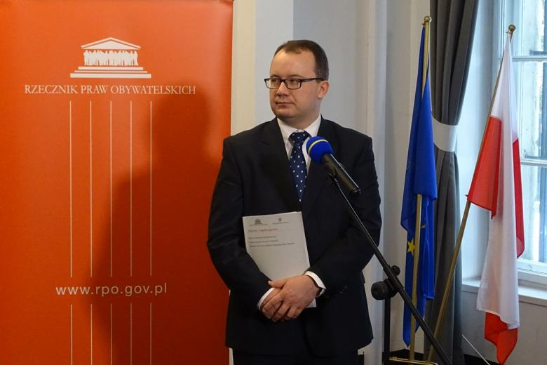 zdjęcie: po lewej stronie stoi pomarańczowy baner, obok mężczyzna w garniturze