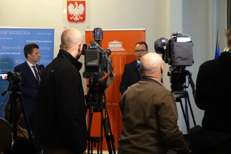 zdjęcie: na pietwszym planie kamery i dziennikarze, w tle dwóch mężczyzn w garniturach
