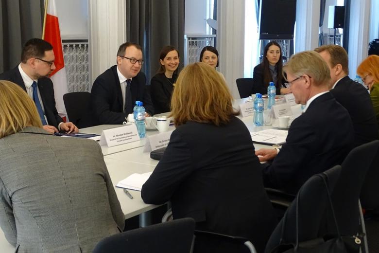 zdjęcie: przy białych stołach ustawionych naprzeciwsiebie siedzi kilka osób