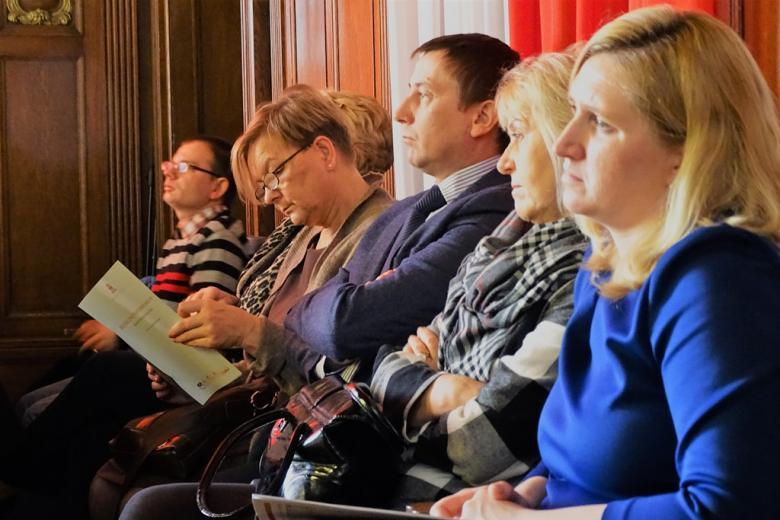 zdjęcie: kilka osób siedzi, jedna z kobiet oglada broszurę