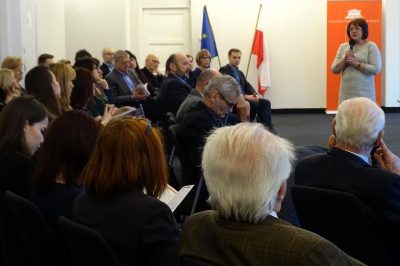 zdjęcie: po lewej stronie widać kilkadziesiąt osób siedzących na krzesłach, po prawej stronie stoi kobieta w jasnej sukience