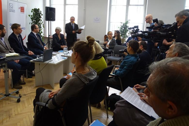 zdjęcie: po lewej stronie siedzą na krzesłach trzej mężczyźni i kobieta na przeciw nich kilkanaście osób i kamery
