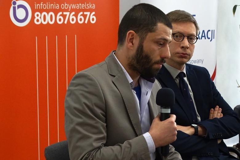 zdjęcie: dwóch mężczyzn siedzi na krzesłach, jeden z nich mówi do mikrofonu