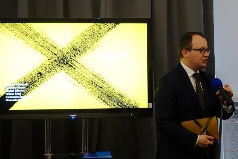 zdjęcie: mężczyzna w garniturze stoi i mówi do mikrofonu, za nim ekran, na którym wyświetla się okładka raportu