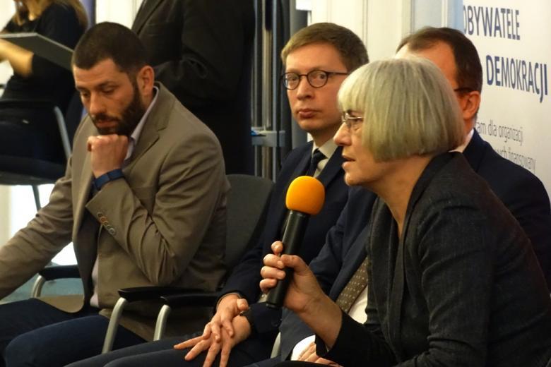 zdjęcie: na krzesłach siedzi trzech mężczyzn i kobieta, która mówi do mikrofonu