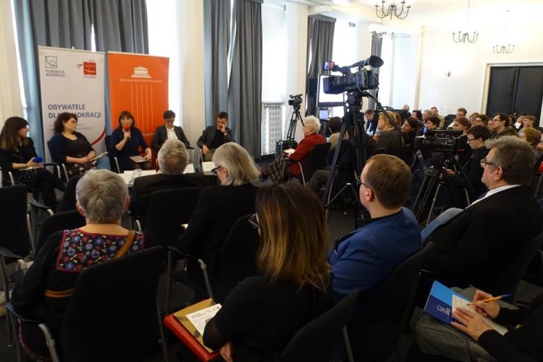 zdjęcie: pięć osób siedzi przed widownią, jedna z kobiet mówi do mikrofonu